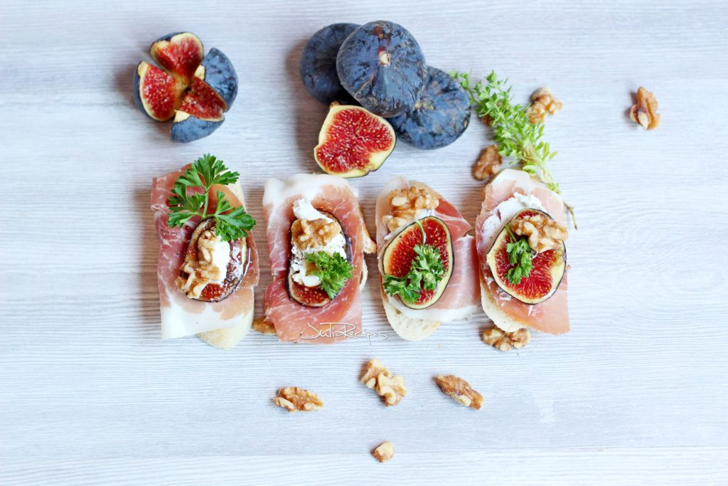 crostini topped with slice of prosciutto and goat cheese