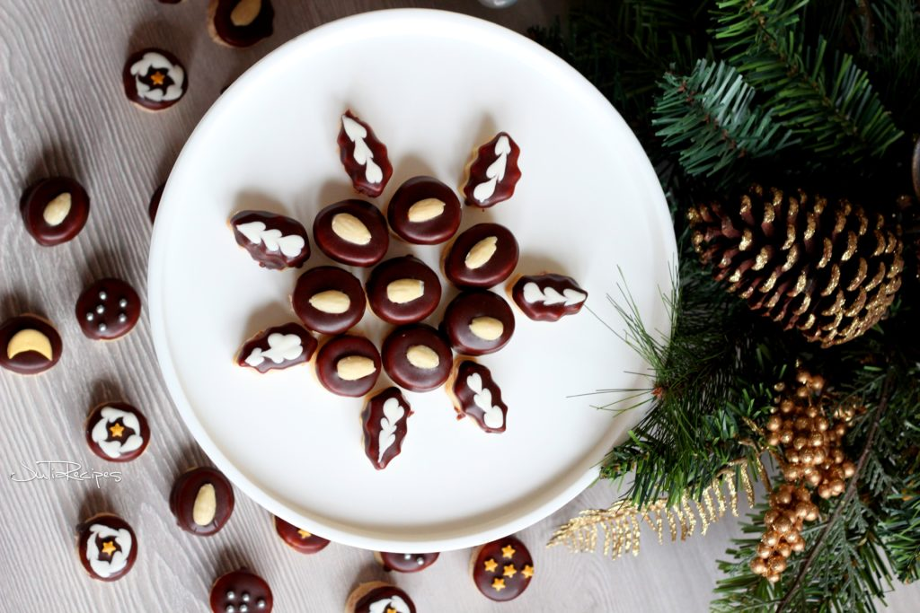 chocolate cookies with almond on top on white plate