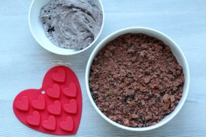 chocolate cake mix in one bowl and oreo buttercream in another bowl with heart mold