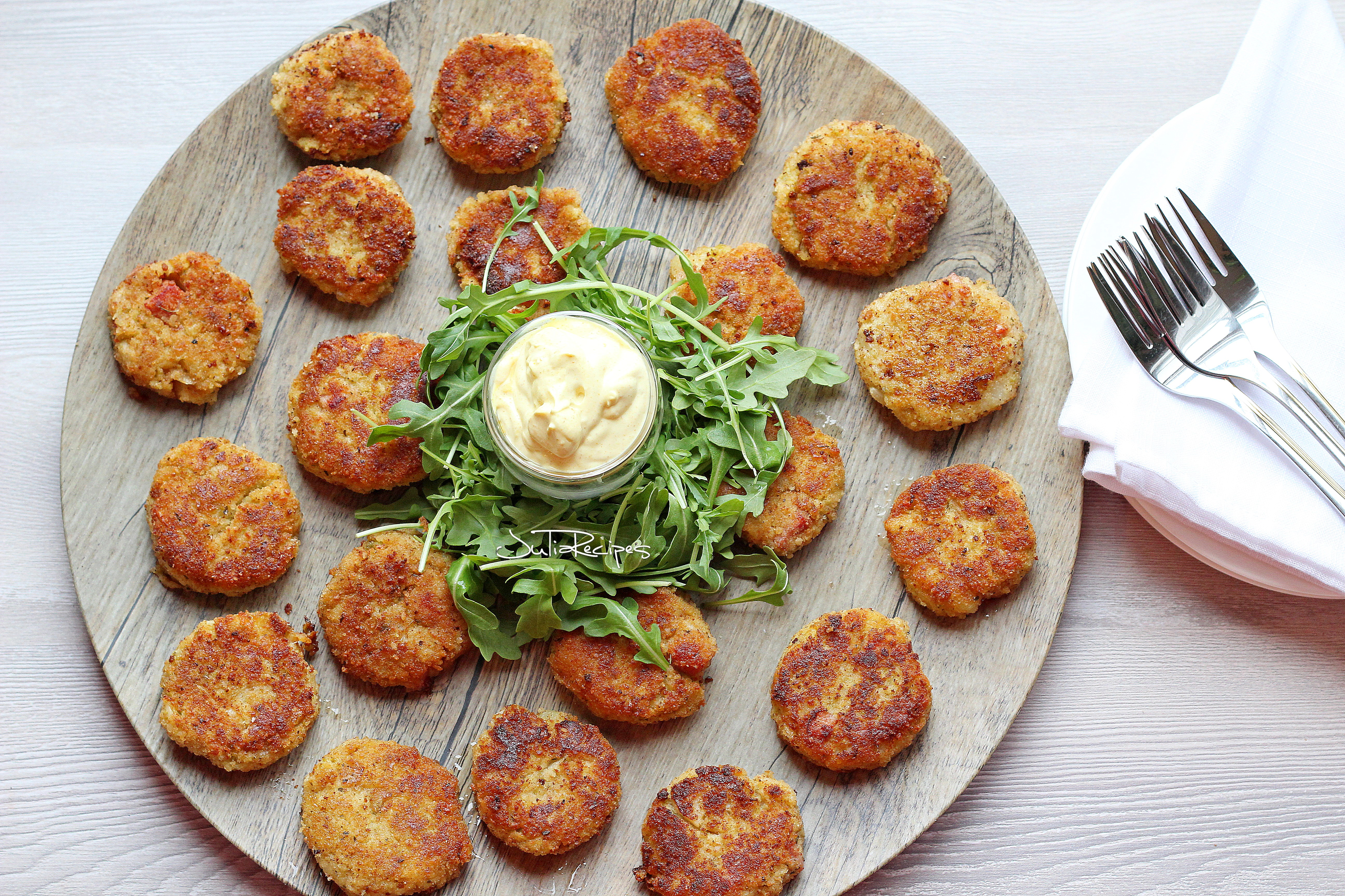 Cauliflower fritters on plate with curry sauce and arugula salad in the middle