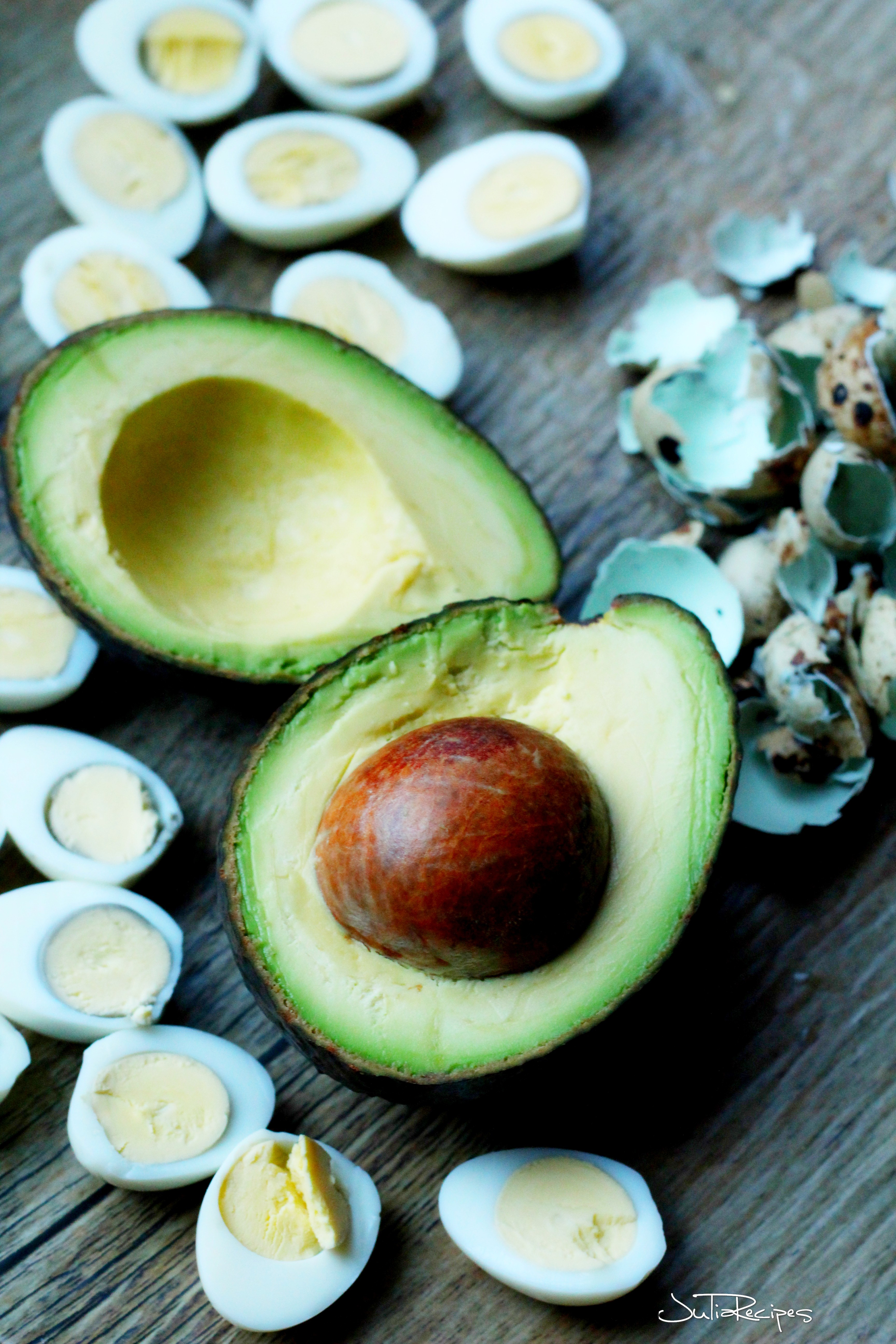 avocado cut in half surrounded with hard boiled quail eggs