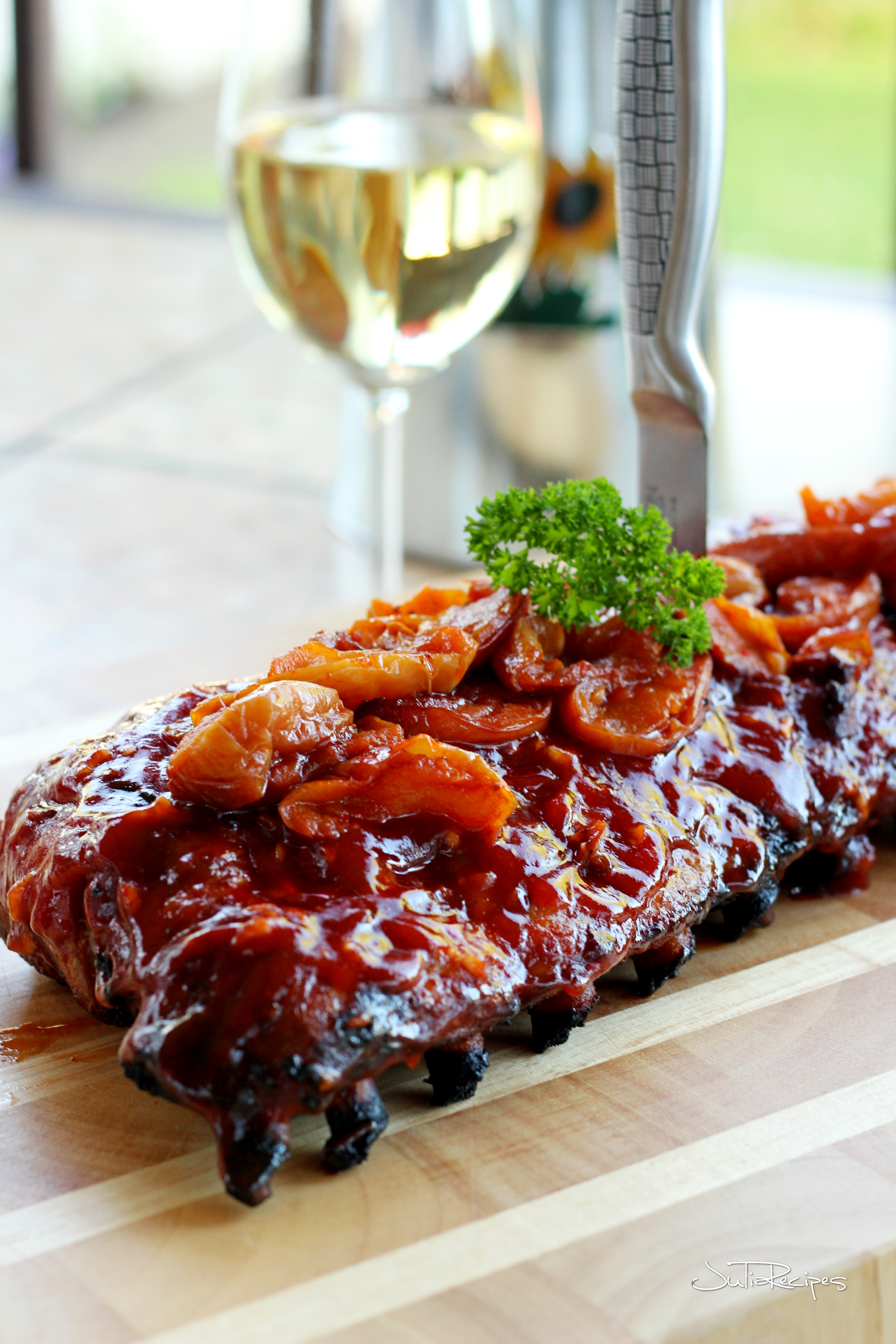 apple smoked pork ribs on wooden plank with glass of white wine