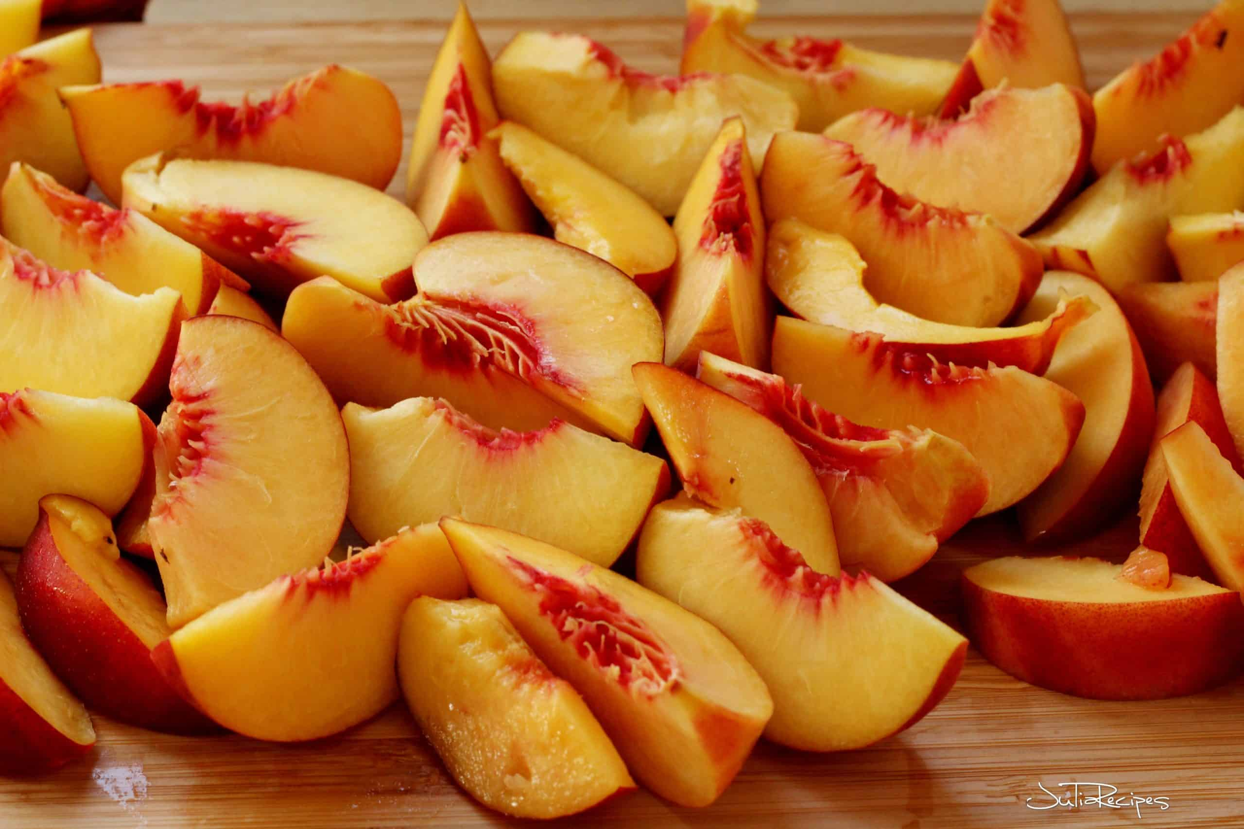sliced fresh peaches on wooden board