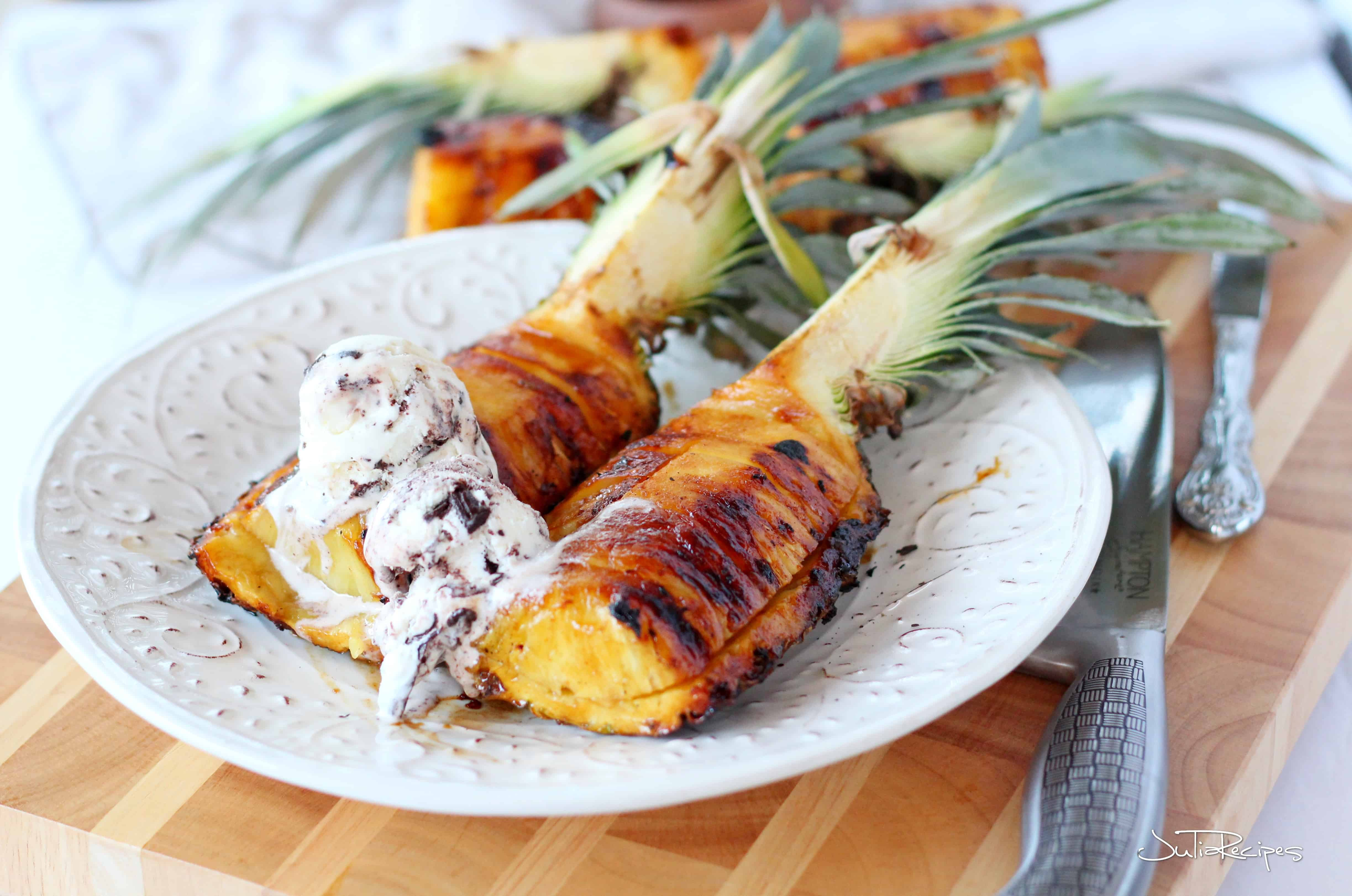 Grilled pineapple wedges on white plate with ice cream