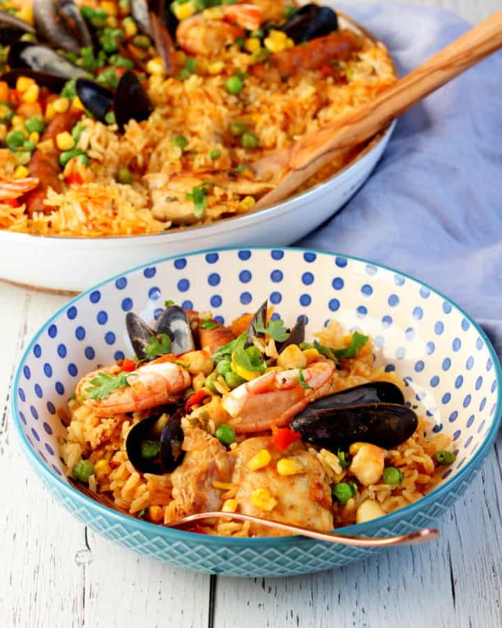 colorful rice with seafood on blue dotted plate with paella pan in background