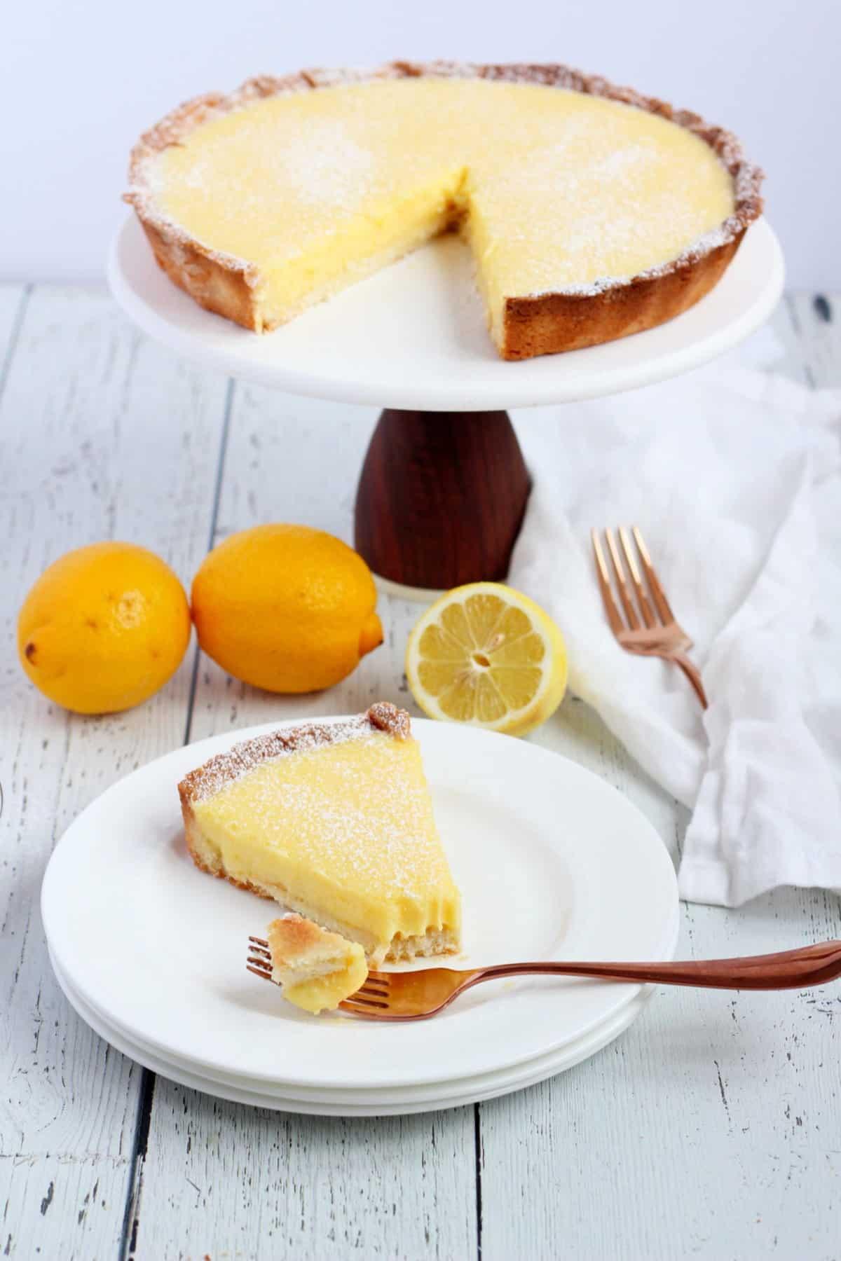 Lemon tart slice with fork and lemons