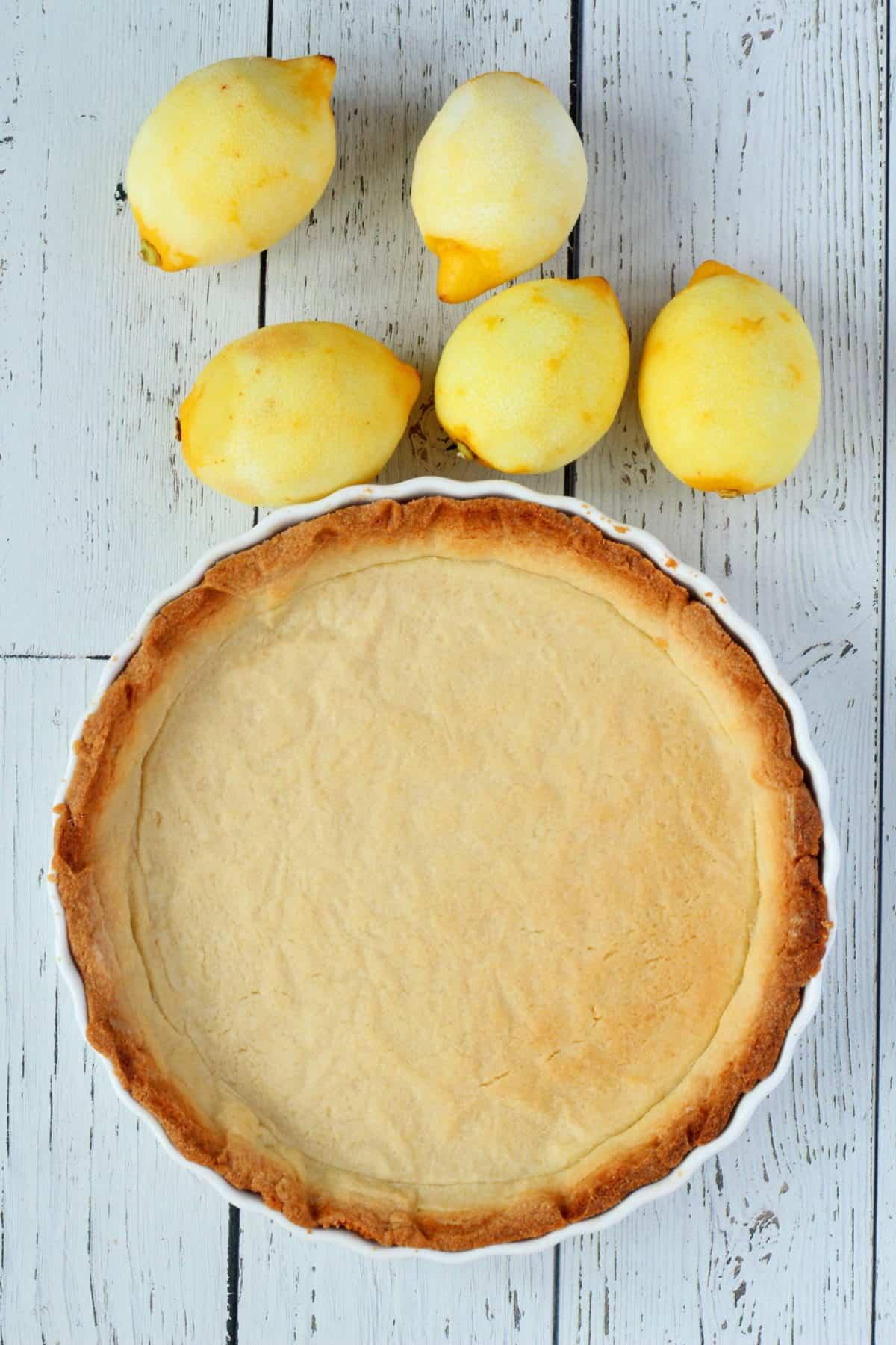 Lemon tart sprinkled with sugar in white dish