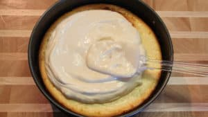 sour cream mixture on cheesecake