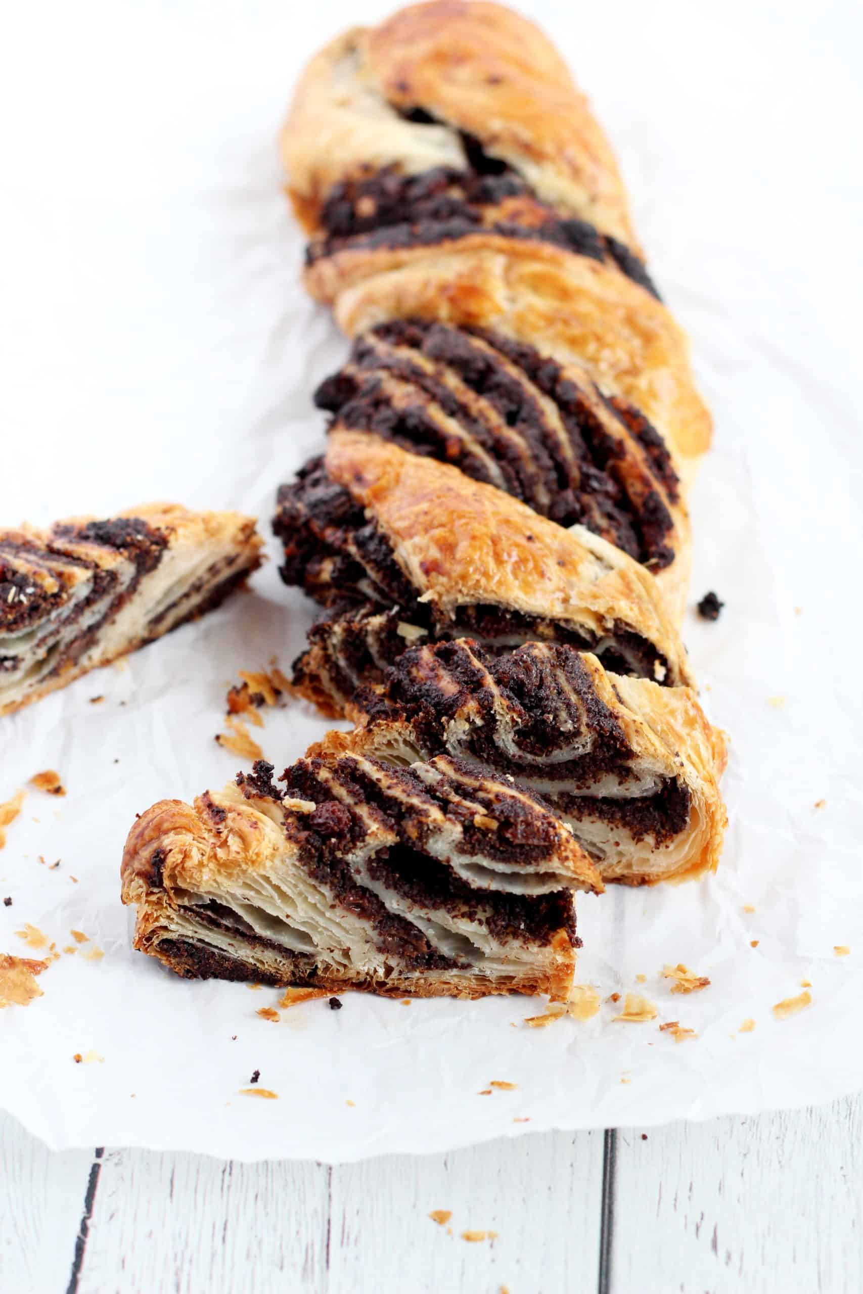 chocolate and poppy seed cut on pieces babka on parchment paper