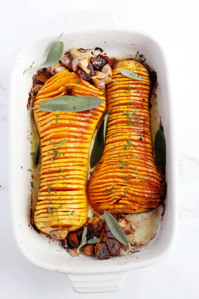 baked butternut squash cut in half and sliced thinly and placed in white ceramic baking sheet