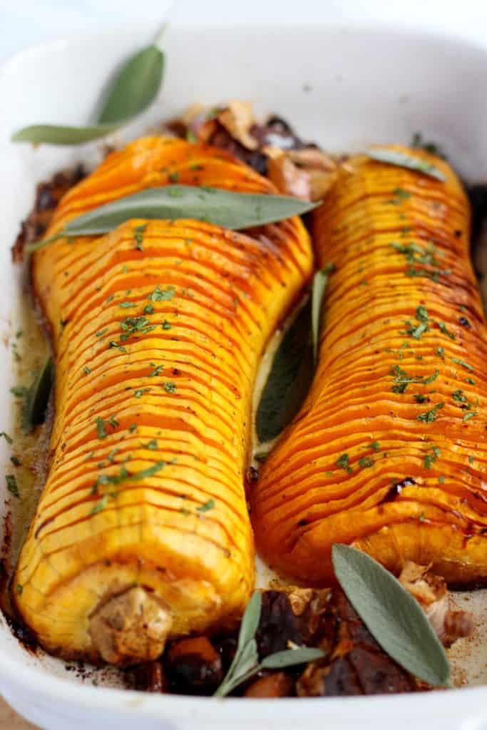 baked hasselback butternut squash with sarfan leaves and galic bulbes