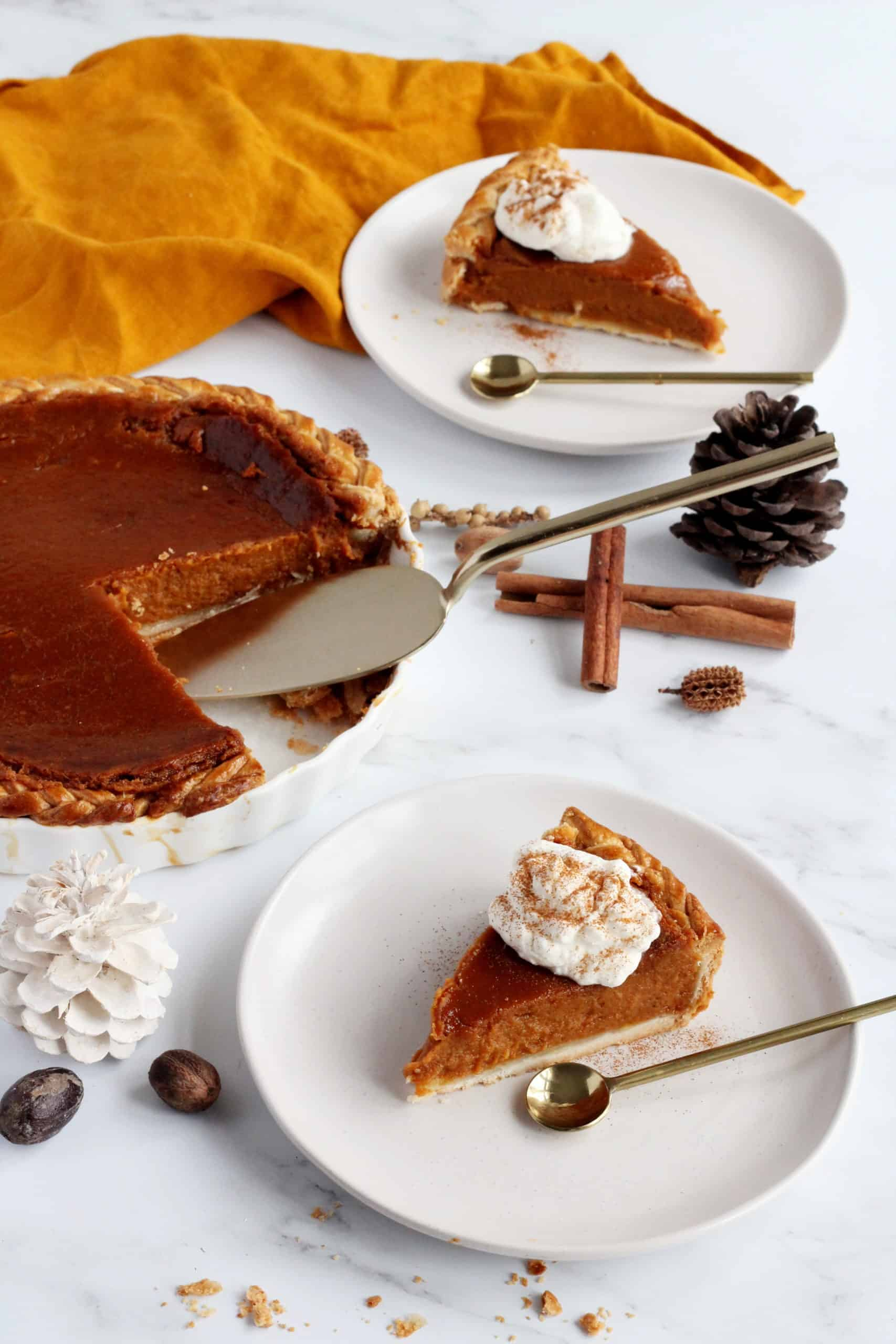 Layout with pumpkin pie in a pan with two white plates and slices of pumpkin pie on it