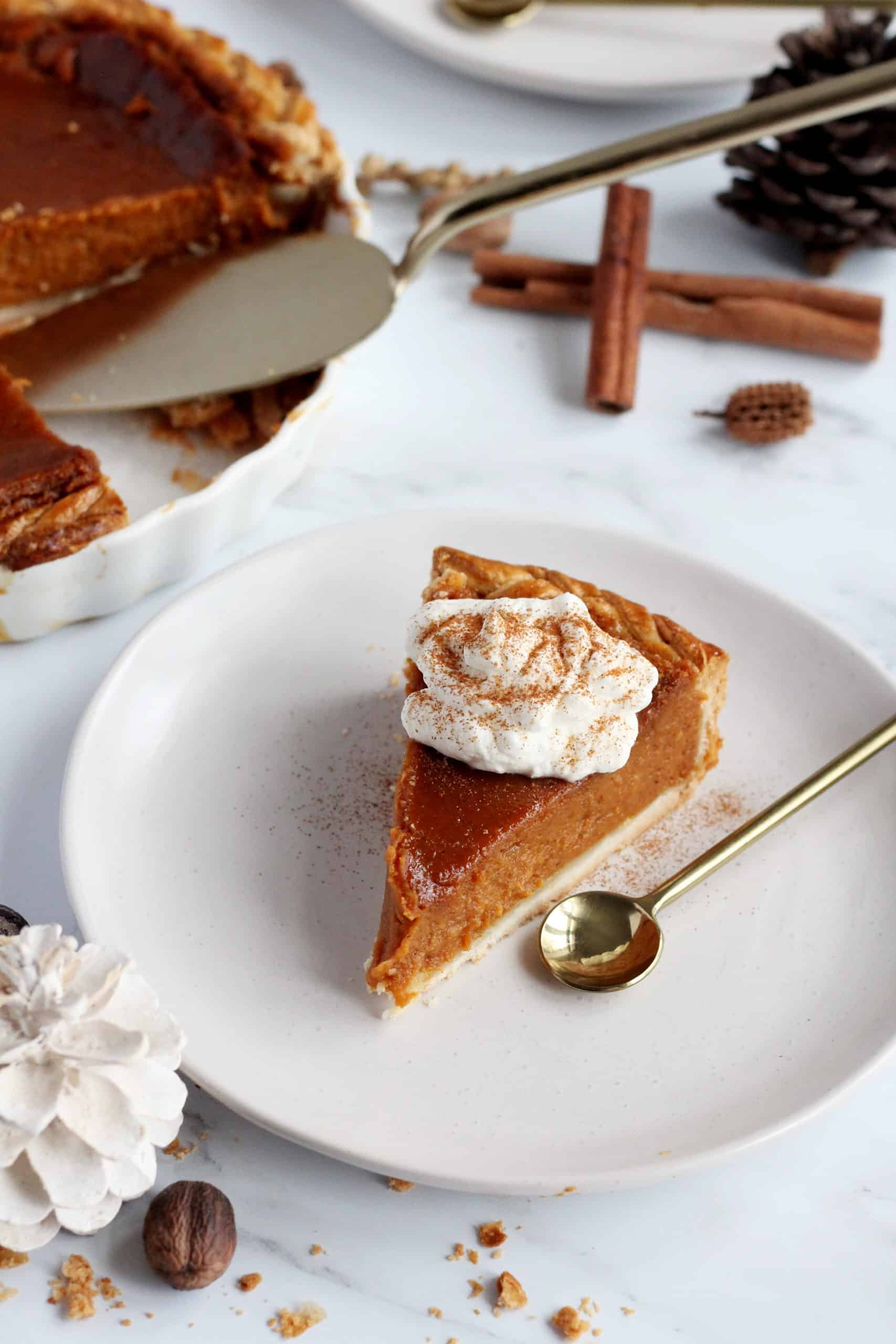 slice of pumpkin pie with the whole pie in the background and fall decoration
