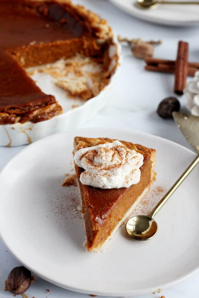 pumpkin pie with whipped cream on top dollop on top served on white plate