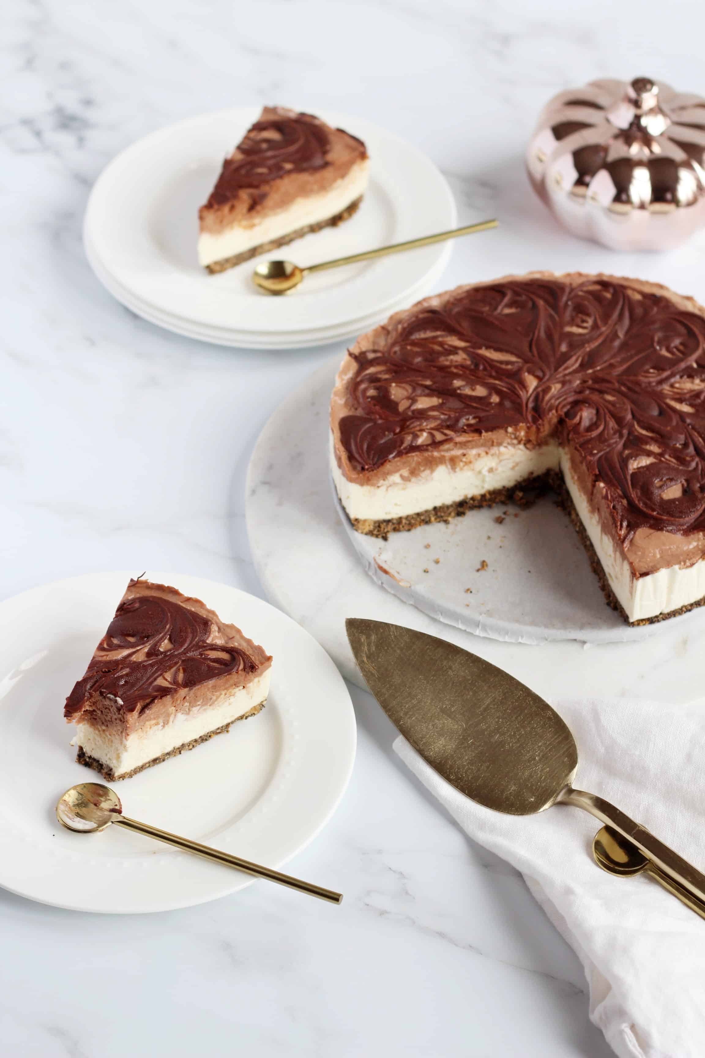 Nutella swirl Cheesecake cut out two slices on white plates with golden spoons