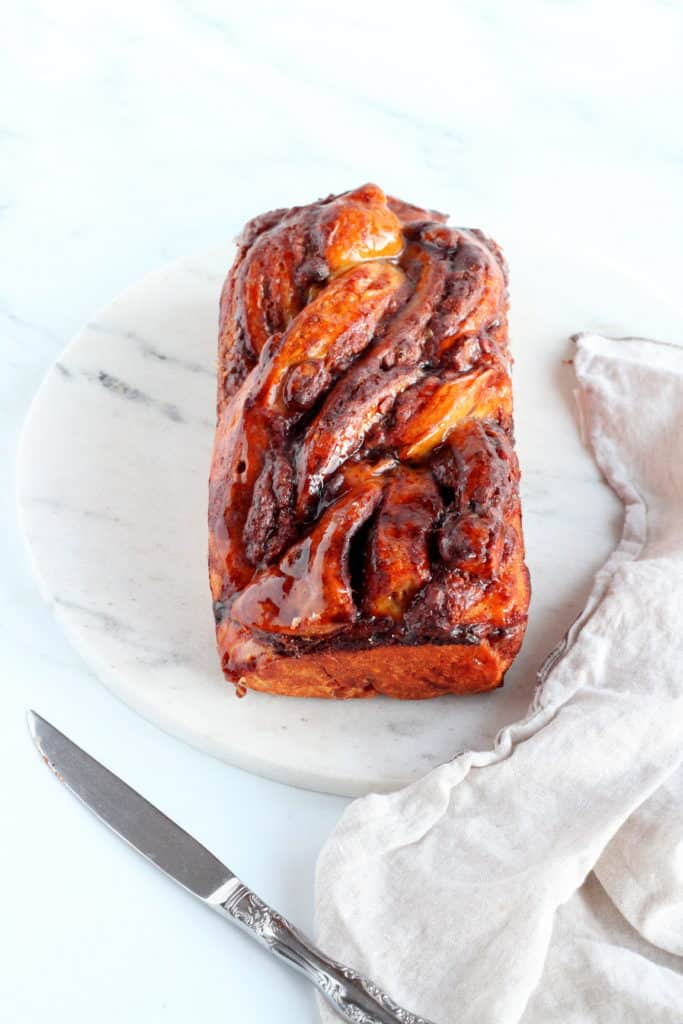 loaf of chocolate babka with almond filling on marble tray
