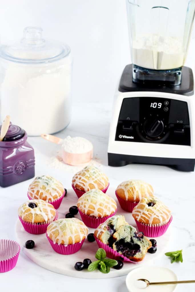 Few blueberry muffins with lemon glaze laying on the marble board with Vitamix blender behind.