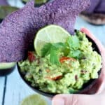 Simple guacamole dip inside woden bowl with tortilla chips and slice of lime
