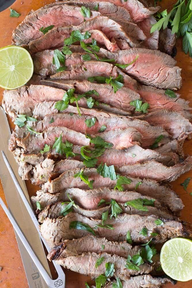 grilled flank steak on wooden board