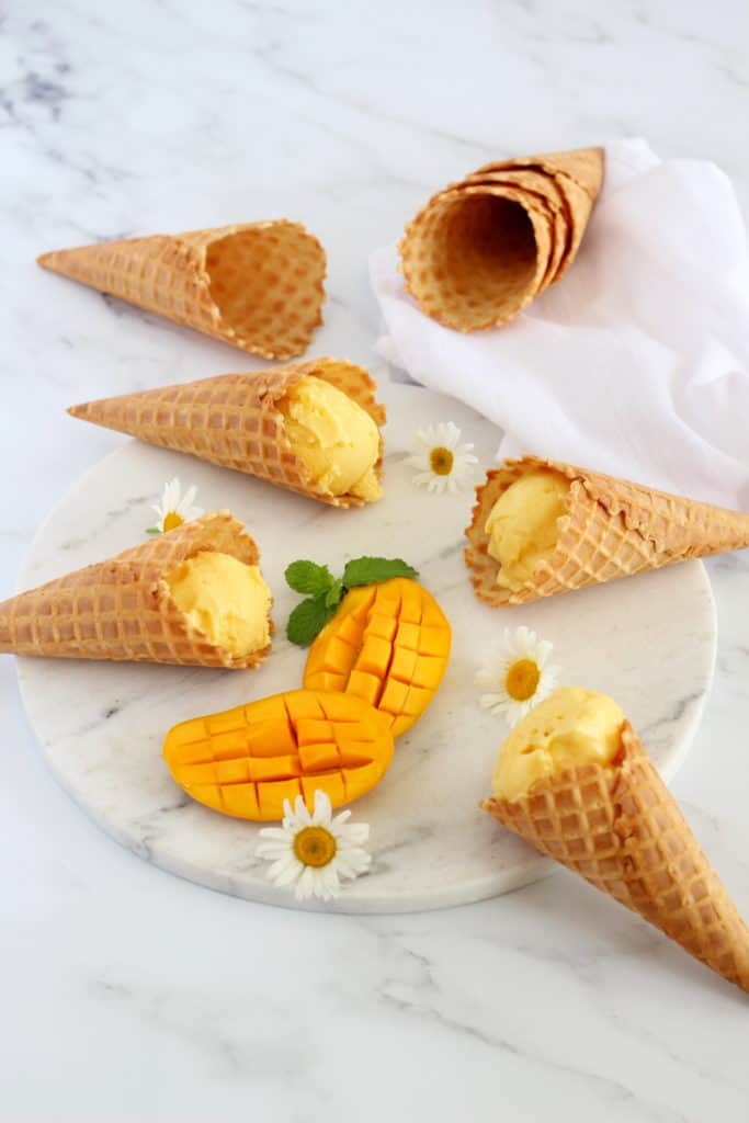 mango sherbet in waffle cones on marble stand