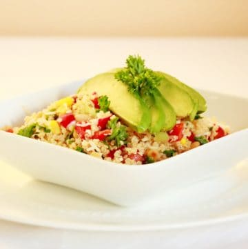 quinoa salad in white bowl topped with avocado