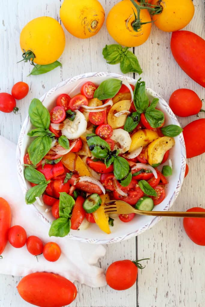 tomato salad with basil and cucumber in white plate