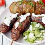 close up of bbq'd kebaba with roasted potatoes and cucumber salad with feta cheese